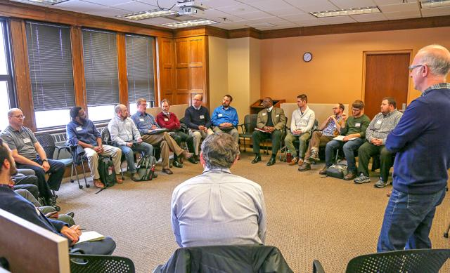 Circle of 20+ men in room listening to presentation by man standing