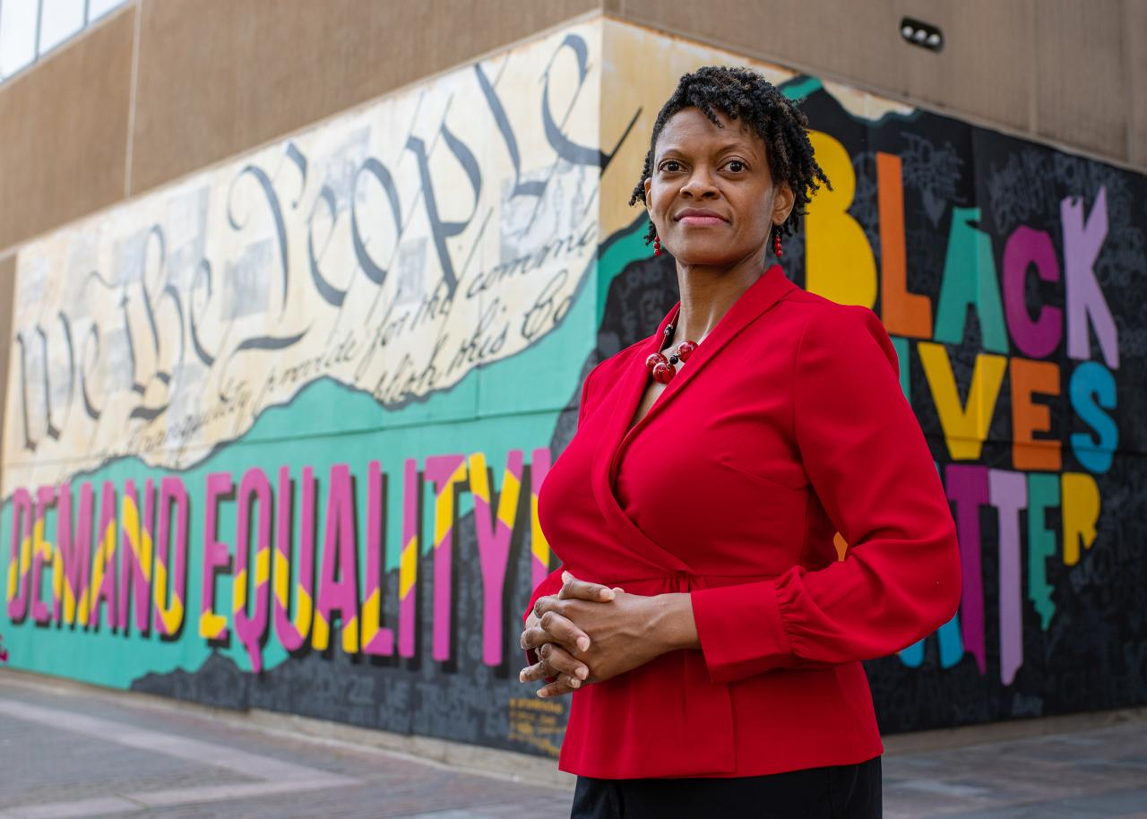 Andrea Williams standing in front of Black Lives Matter street art