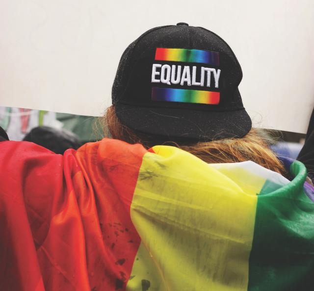 Person wearing LGBTQ+ Equality hat