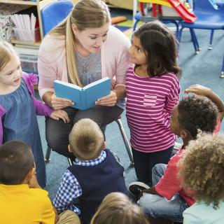 Child care worker reading to group of children